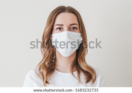 Portrait of a young girl in a medical mask isolated on a white wall background. Young woman patient, copy space