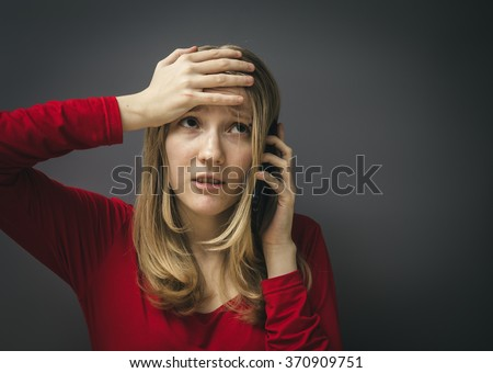 Portrait of a young girl in a red dress on a gray background. Bad news