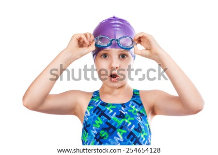 Portrait of a young girl in goggles and swimming cap. surprised girl