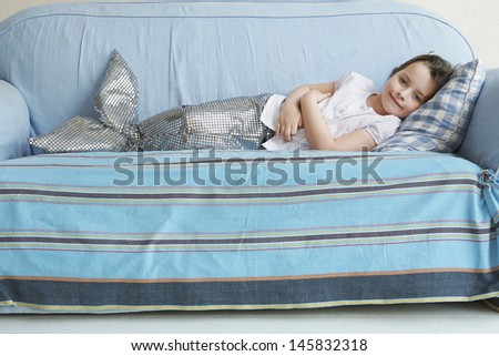 Portrait of a young girl in mermaid costume lying on sofa at home