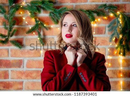 Portrait of a young girl in red coat at Christmas lights background #1187393401