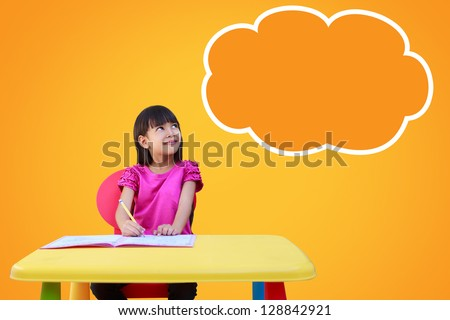 Portrait of a young girl in school at the desk. Daydreaming. Blank cloud with copyspace for your text and logo