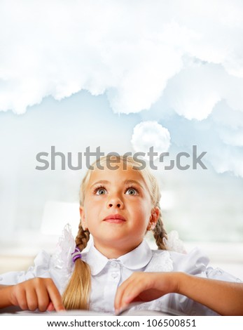 Portrait of a young girl in school at the desk. Vertical Shot. Daydreaming. Blank cloud with copyspace for your text