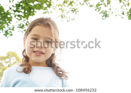 Portrait of a young girl in the park smiling at the camera.