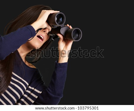 portrait of a young girl looking through binoculars over a black background