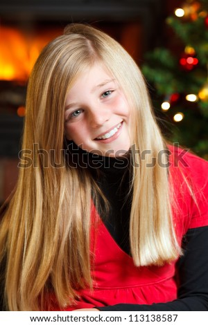 portrait of a young girl on christmas eve christmas tree in background