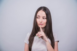 portrait of a young girl putting her finger to her mouth as a sign of silence and secrecy on a white background