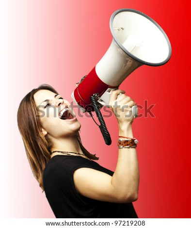 portrait of a young girl shouting with a megaphone over a red background - stock photo