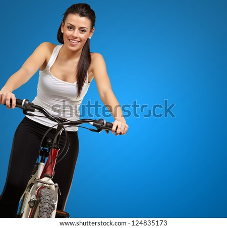 Portrait of a young girl sitting in bicycle isolated on blue background
