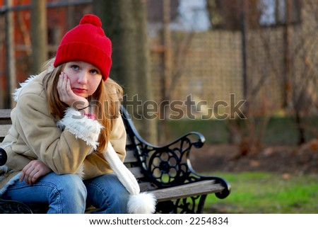 Portrait of a young girl sitting on a bench outside