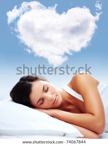 Portrait of a young girl sleeping on a pillow with heartshaped cloud over her - stock photo