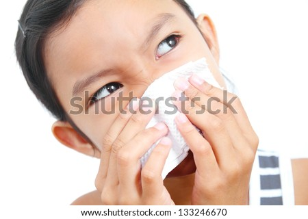 Portrait of a young  girl sneezing on a tissue paper.