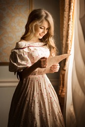 Portrait of a young girl standing near the window and smiling reading a letter. Historical reconstruction