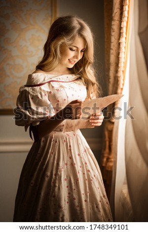Portrait of a young girl standing near the window and smiling reading a letter. Historical reconstruction Stockfoto ©