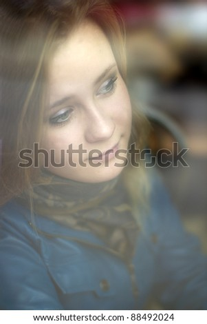 Portrait of a young girl through a window glass