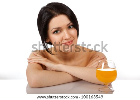 Portrait of a young girl with a glass of orange juice on a white background