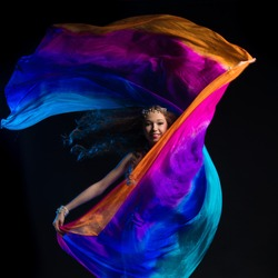 Portrait of a young girl with long hair in a turquoise costume oriental dancer with a multicolored shawl posing and dancing on a black background in the scenic blue light