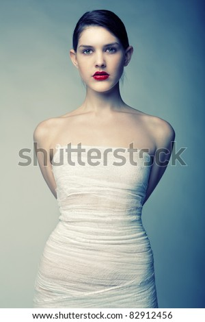 Portrait of a young girl wrapped in bandages with big red lips