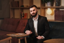 Portrait of a young handsome bearded man. A businessman in a suit sits at a table in a cafe or restaurant and drink coffee.