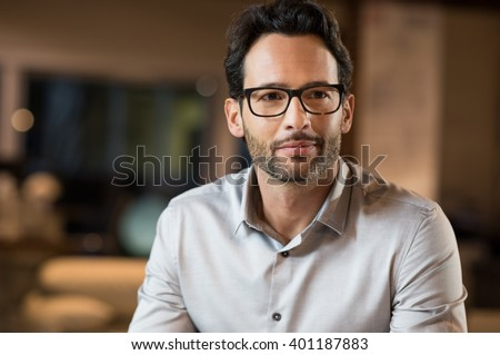 Portrait of a young handsome businessman wearing glasses. Close up of smiling business man wearing eyeglasses. Thinking business man wearing glasses sitting in office.