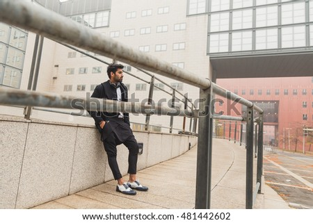 Portrait of a young handsome Indian man posing in an urban context #481442602