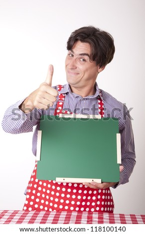 Portrait of a young handsome male cook holding a green board.