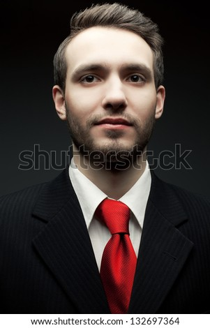 Portrait of a young handsome man (businessman) in black suit with trendy red tie smiling and looking at somebody or something. Close up. Studio shot