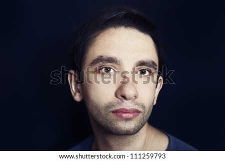 portrait of a young handsome man in a blue shirt on a black background close up