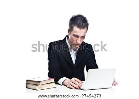 Portrait of a young handsome man in the strict business suit, sitting at a table and a laptop running