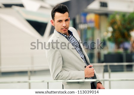 Portrait of a young handsome man, model of fashion, wearing jacket and shirt in urban background