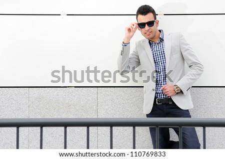 Portrait of a young handsome man, model of fashion, wearing tinted sunglasses