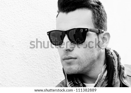 Portrait of a young handsome man, model of fashion, wearing tinted sunglasses in urban background
