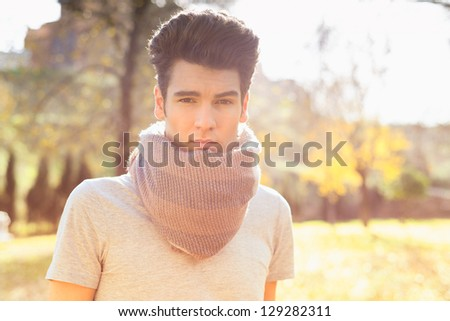 Portrait of a young handsome man, model of fashion, with modern hairstyle in the park