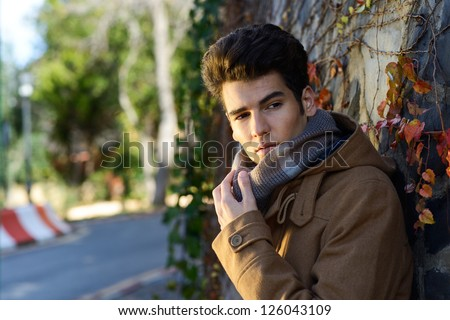 Portrait of a young handsome man, model of fashion, with toupee in a park