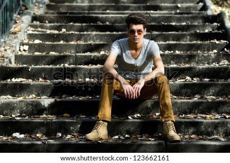 Portrait of a young handsome man, model of fashion, with toupee in stairs