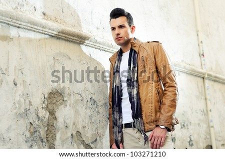 Portrait of a young handsome man, model of fashion, with toupee in urban background