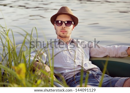 Portrait of a young handsome man resting in a boat on the lake, sunny summer day
