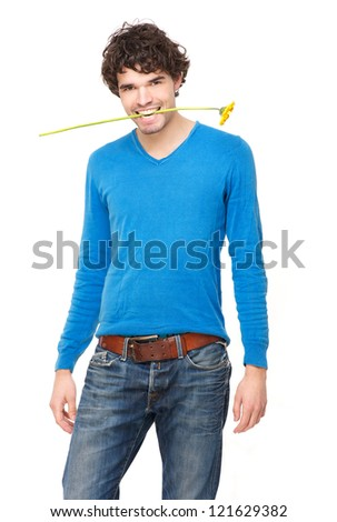 Portrait of a young handsome man wearing a blue sweater with a yellow flower in his mouth. Isolated on white background - stock photo