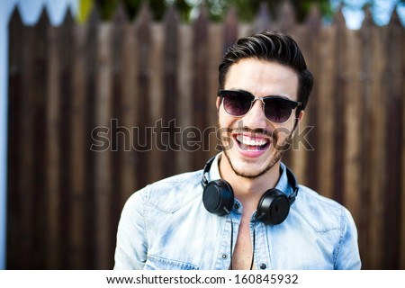 Portrait of a young handsome man with toupee and headphones in urban background #160845932