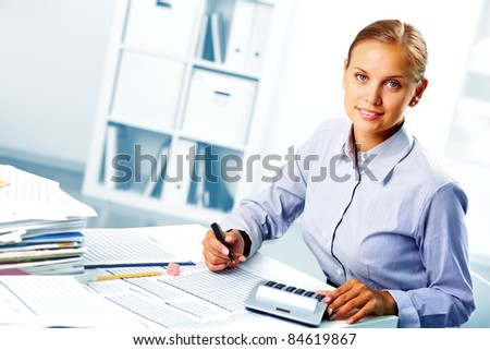 Portrait of a young happy businesswoman looking at camera while working in office