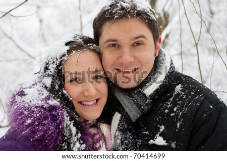 Portrait of a young happy couple in winter park