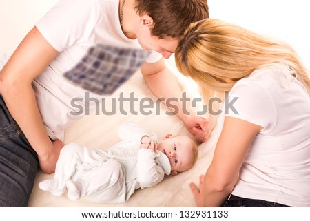 Portrait of a young happy family lying, parents with baby isolated on white