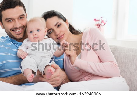 Portrait of a young happy family with the kid at home