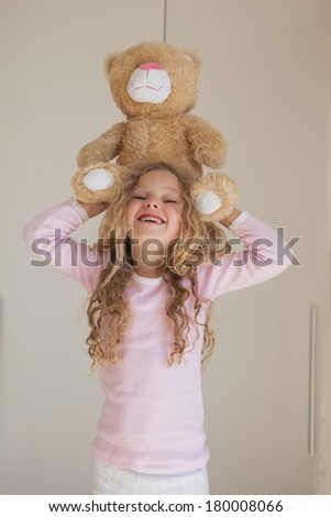 Portrait of a young happy girl holding stuffed toy over head at home