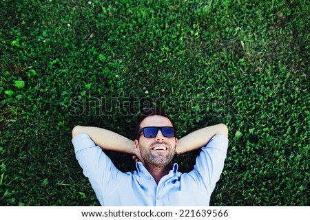 Portrait of a young happy man relaxing on the grass with his hands under the head #221639566