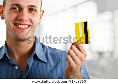 Portrait of a young happy man showing a credit card