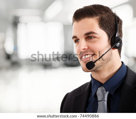 Portrait of a young happy phone operator. Bright blurred background. - stock photo
