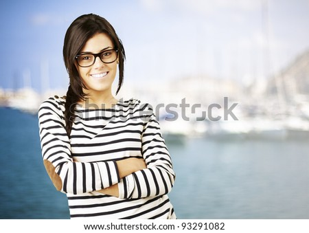 portrait of a young happy woman posing against a harbor on a sunny day background