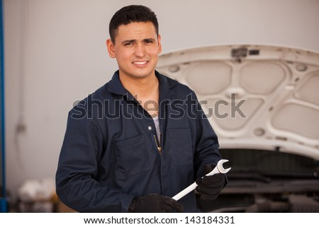 Portrait of a young Hispanic mechanic holding a wrench at an auto shop