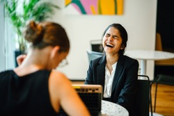 Portrait of a young Indian Asian professional woman in an interview or meeting. She is laughing out loud naturally as she engages with her meeting partner, a Caucasian white woman.